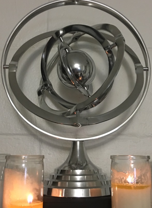 A close-up of the armillary sphere on my altar. It is on top of a black wooden box, and flanking it on either side at the bottom are two burning jar candles.